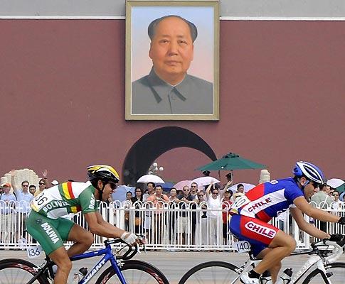 Ciclistas pedalam sob o olhar de Mao (Foto EPA)