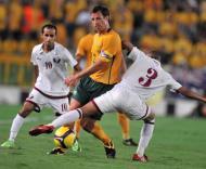 Lucas Neill (Austrália) entre dois jogadores do Qatar