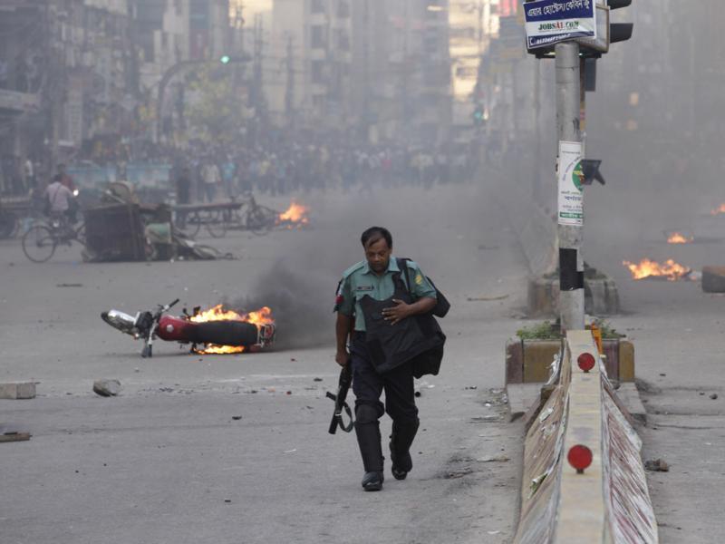 Polícia caminha entre os destroços de protestos no Bangladesh. REUTERS/Andrew Biraj
