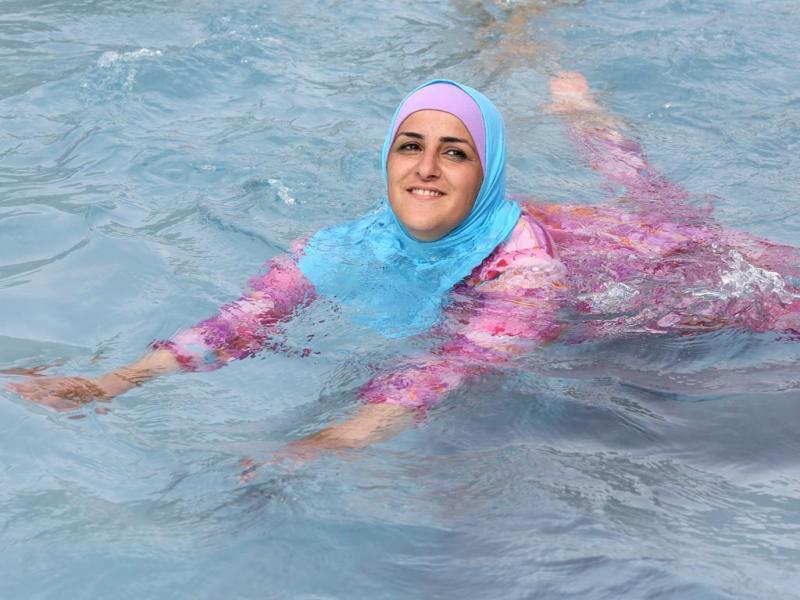 Mulher toma banho na Alemanha vestida com um burkini