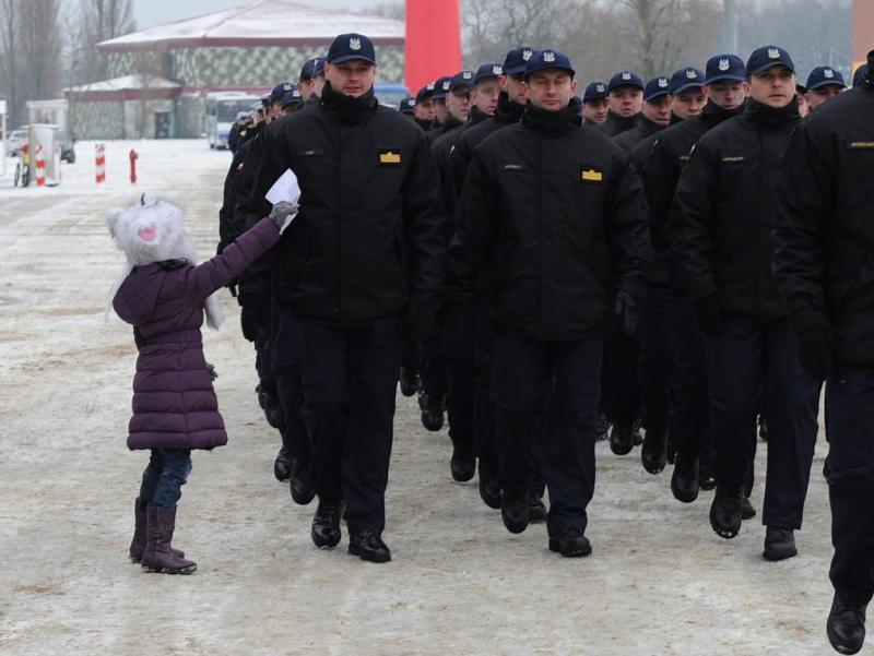 Menina entrega bilhete de despedida ao pai que participa em missão da NATO (EPA/MARCIN BIELECKI)