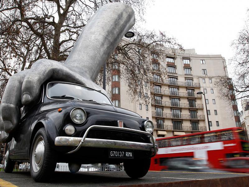 Um Fiat 500 agarrado por uma mão de alumínio é visto na escultura do artista italiano Lorenzo Quinn Vroom Vroom em Londres  (REUTERS)