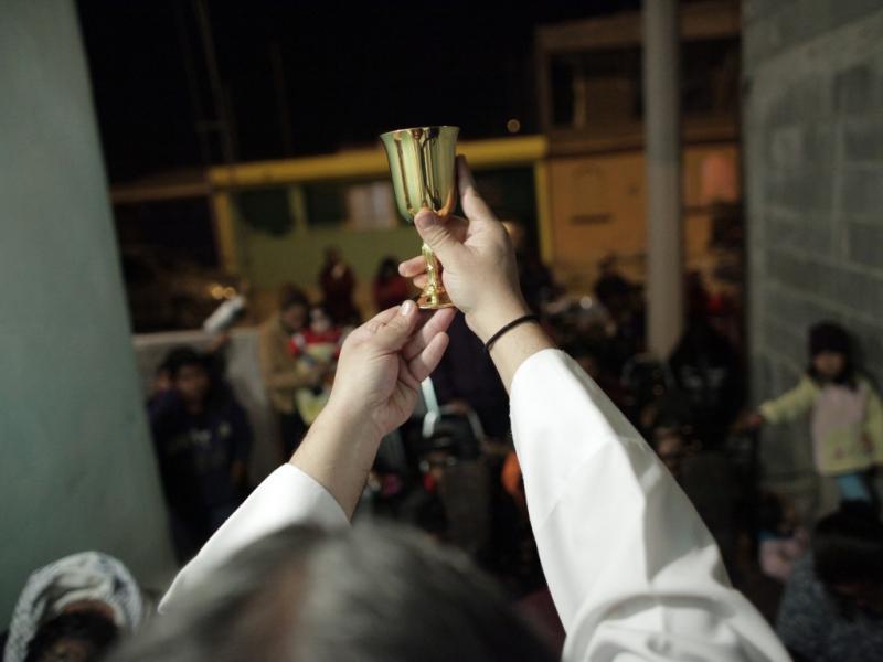 Em Saltillo, o padre Gofo celebra missas fora da igreja, como esta, à porta de uma casa (Daniel Becerril/Reuters)