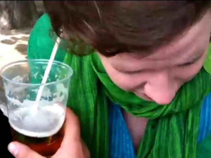 Mulher bebe cerveja pela orelha