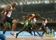 22/8/2004: Francis Obikwelu corta a meta do estádio olímpico de Atenas na segunda posição, conquistando a medalha de prata nos 100 metros (Reuters/Ruben Sprich)
