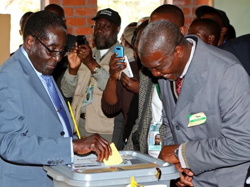 O presidente do Zimbábue, Robert Mugabe, insere o seu voto na urna (Reuters)