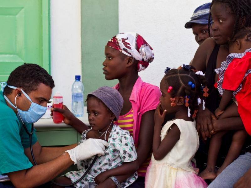 Médico cubano presta auxílio a crianças infetadas (foto: Reuters)