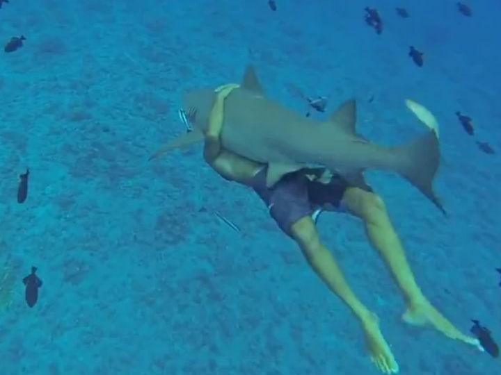 Vídeo mostra homem a nadar agarrado a um tubarão (Foto: Reprodução/YouTube)