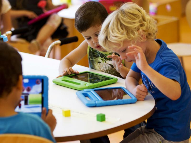 Crianças brincam com iPad (Reuters)