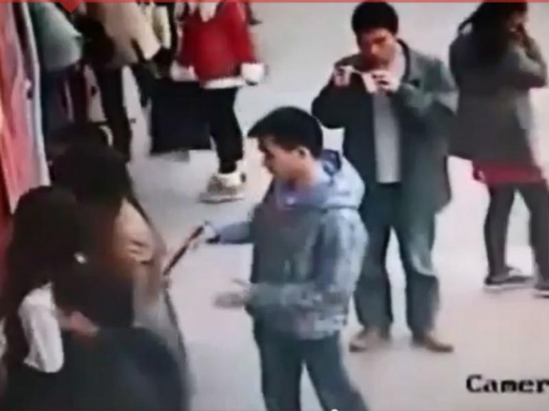 Carteirista com «pauzinhos» rouba telemóvel na China (Reprodução Youtube)