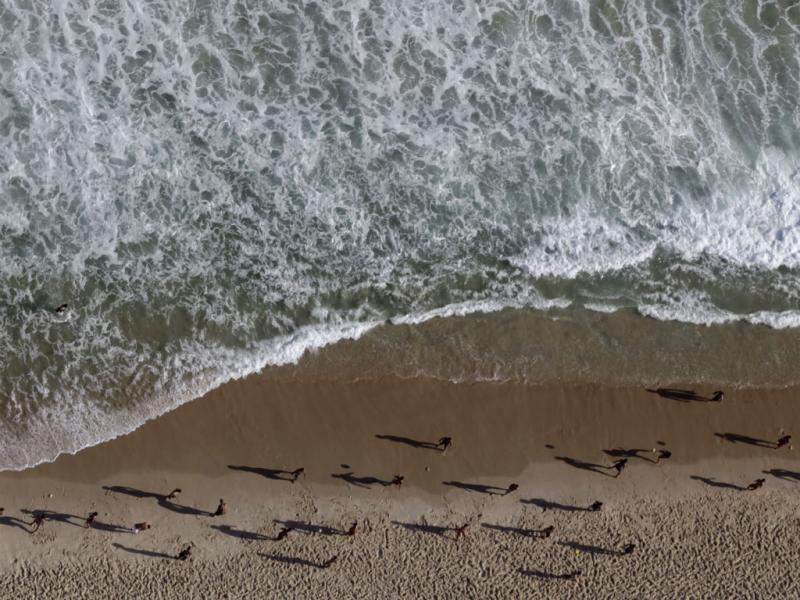Pessoas a jogar futebol numa praia do Rio de Janeiro (Reuters)