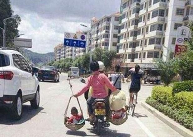 Mulher carrega os filhos em cestas durante viagem de mota