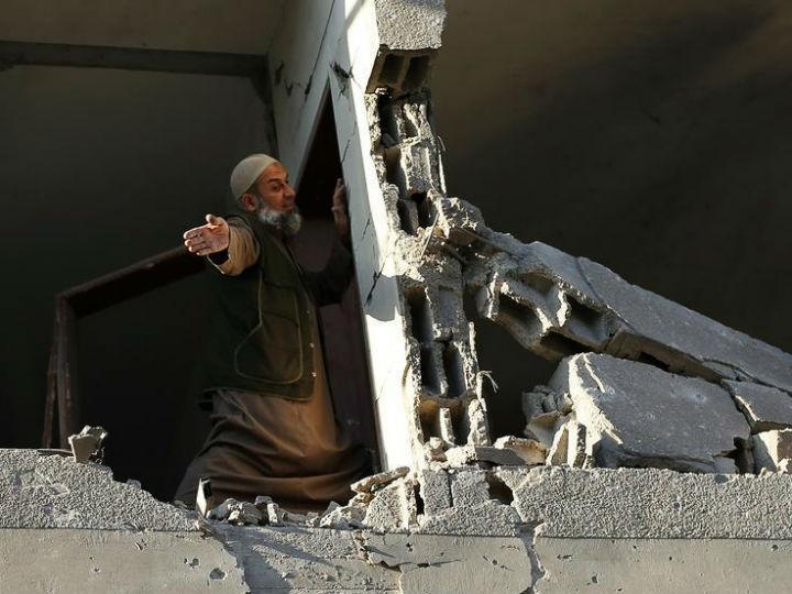 Palestiniano na sua casa em Gaza, destruída pelos ataques aéreos israelitas. REUTERS/Suhaib Salem
