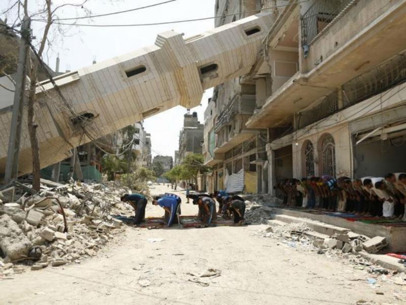 Palestinianos numa oração perante um cenário de destruição em Gaza. REUTERS/Mohammed Salem