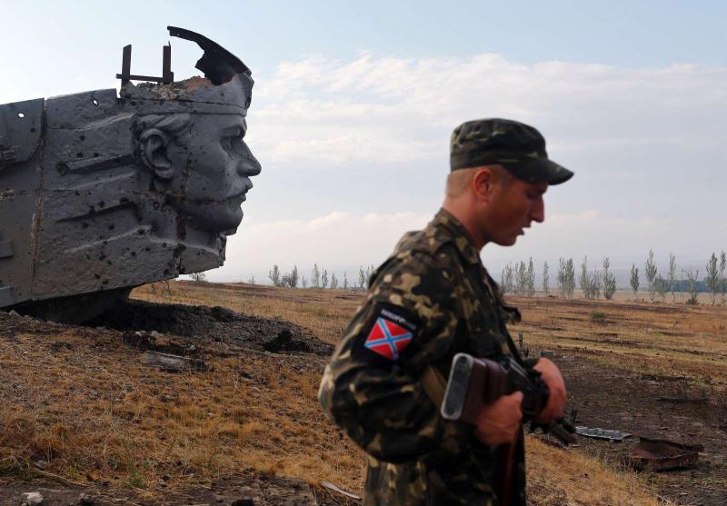 Separatista pró-russo diante de um memorial de guerra destruído pelos confrontos em Donetsk (REUTERS/Maxim Shemetov)