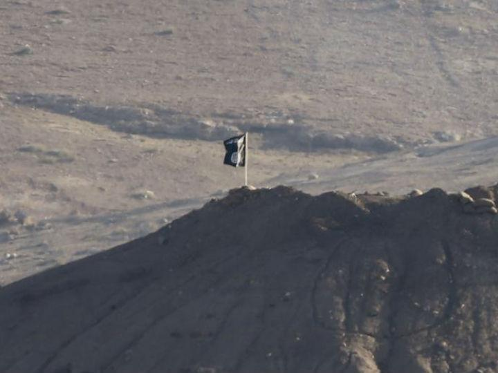 Uma bandeira do Estado Islâmico foi colocada numa colina em Kobani (Reuters)