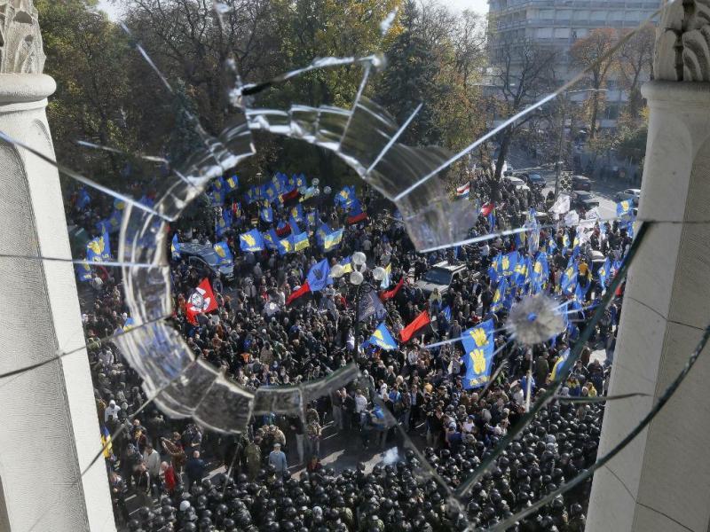Protestos em Kiev vistos por uma janela partida do Parlamento ucraniano (REUTERS)