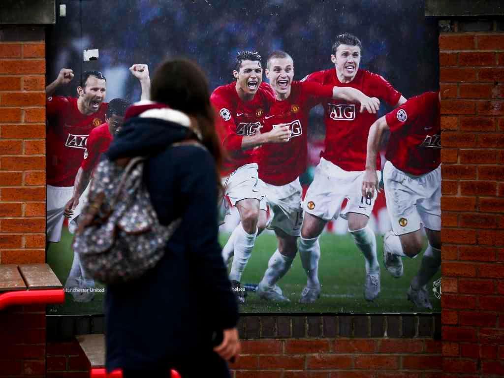 Adepta em Old Trafford vê foto da equipa do ManUtd vencedora da LC em 2008 (Lusa)