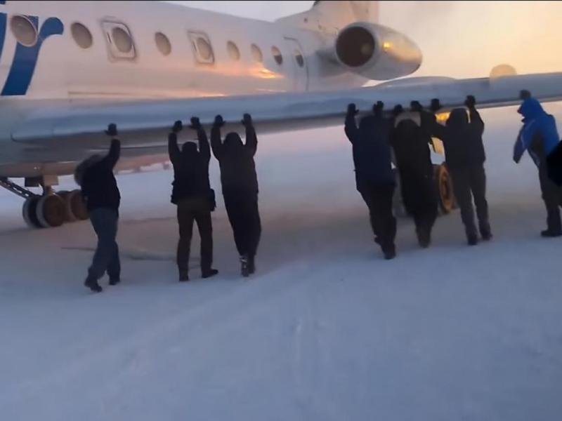 Russos empurram avião preso no gelo