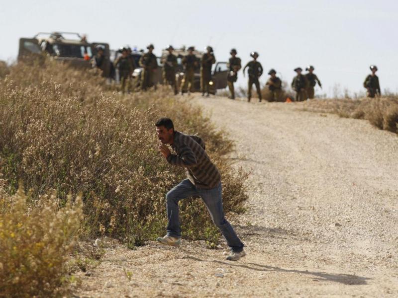 Manifestante palestiniano foge para se esconder das tropas israelitas