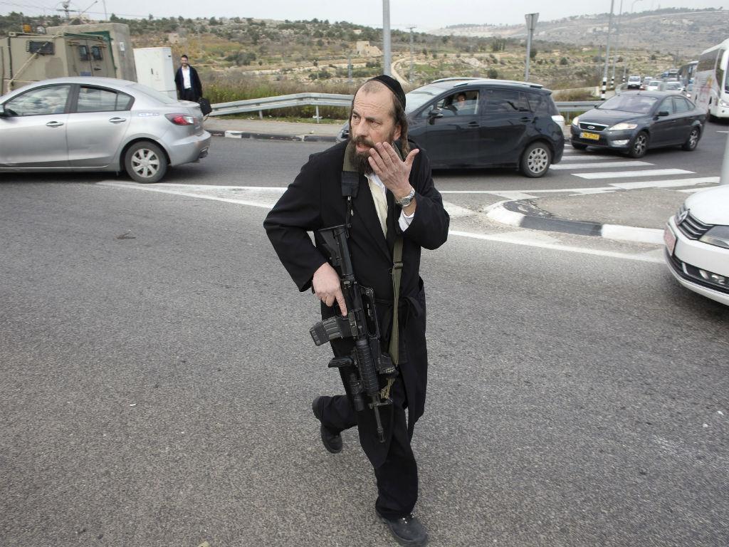 Israelita armado junto ao posto de controlo onde ocorreu um suposto ataque com ácido (REUTERS)