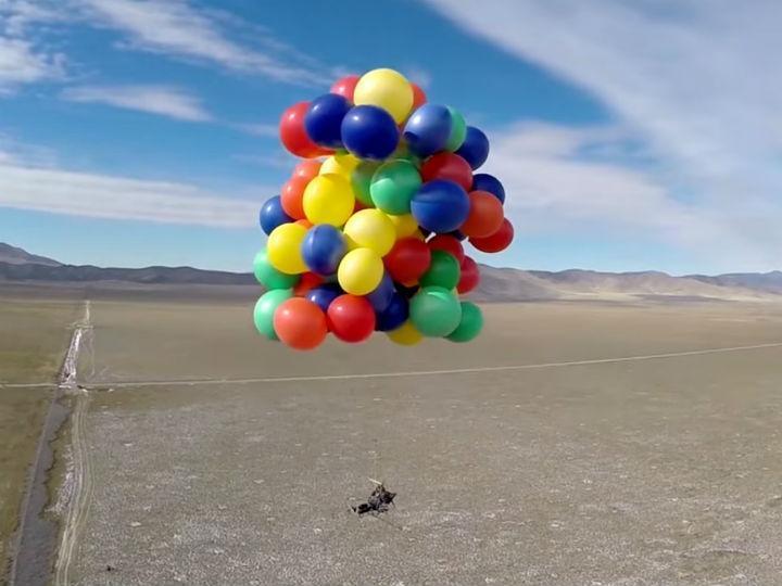 «Voar» numa cadeira preso a 90 balões (Reprodução YouTube)