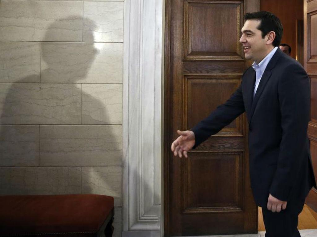 A sombra do presidente do Eurogrupo «cumprimenta» Alexis Tsipras em Atenas. REUTERS/Petros Giannakouris