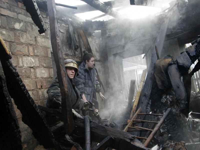 Mulher e bombeiro no meio dos escombros de uma casa (Reuters)