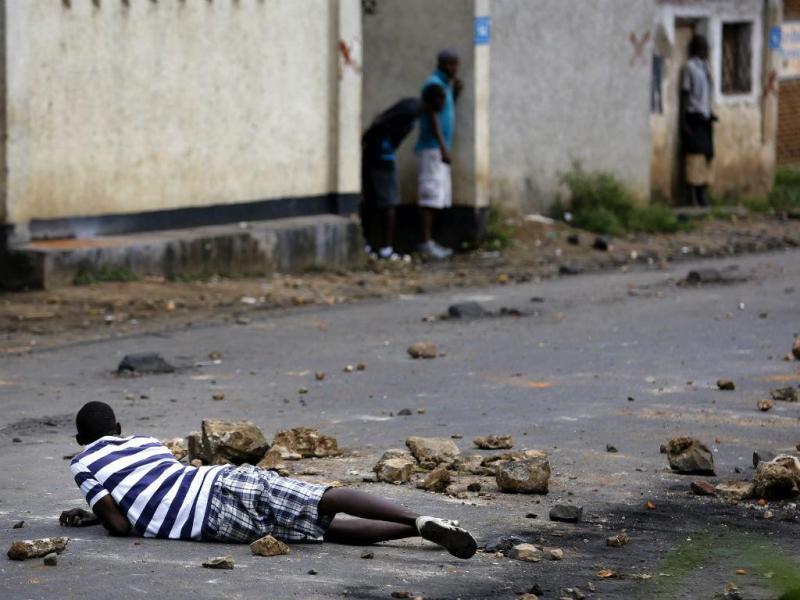 Manifestante tenta proteger-se dos tiros disparados pela polícia durante um protesto no Burundi. EPA/DAI KUROKAWA