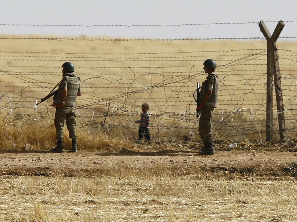 Criança síria espera do outro lado da fronteira para entrar na Turquia (Reuters)