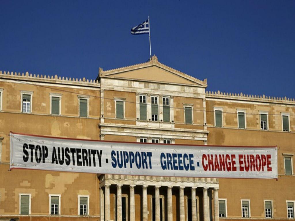 Manifestantes penduram faixa no Parlamento grego, apelando a que a população apoie o governo neste período de negociações com a Europa
