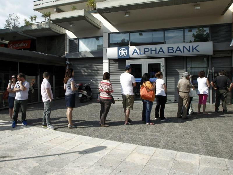 Gregos fazem fila para levantar dinheiro numa caixa multibanco. EPA/ALEXANDROS VLACHOS