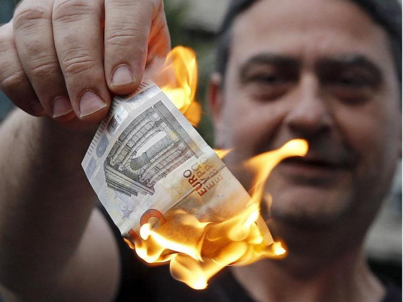 Manifestante anti- austeridade queima uma nota euro durante manifestação no exterior dos gabinetes da União Europeia, em Atenas