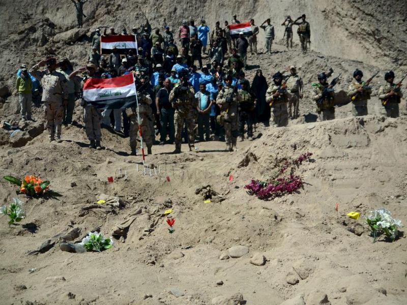 Soldados iraquianos junto a vala comum em Tikrit