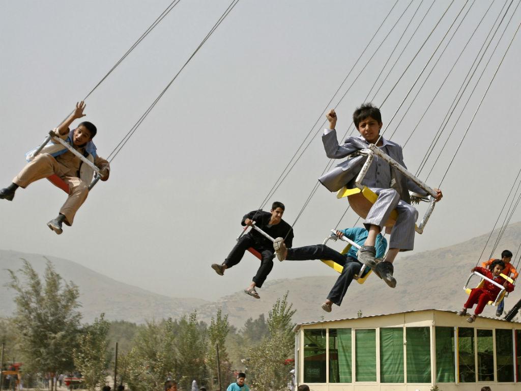 Crianças dão uma volta num carrossel suspenso no ar [Fonte: REUTERS/Omar Sobhani]