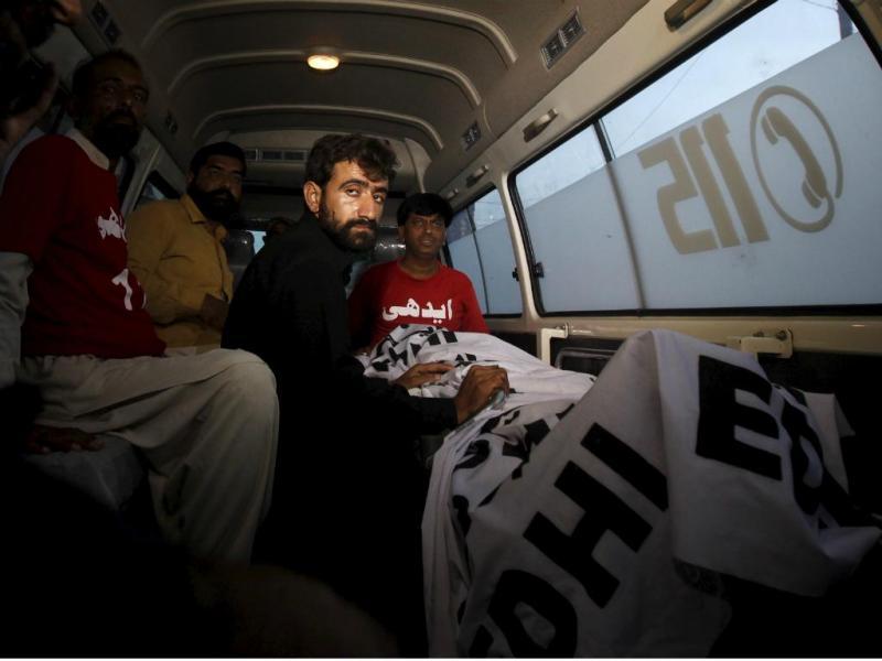Abdul Majeed, irmão de Shafqat Hussain, ao lado do corpo de Shafqat depois deste ter sido executado [Reuters]