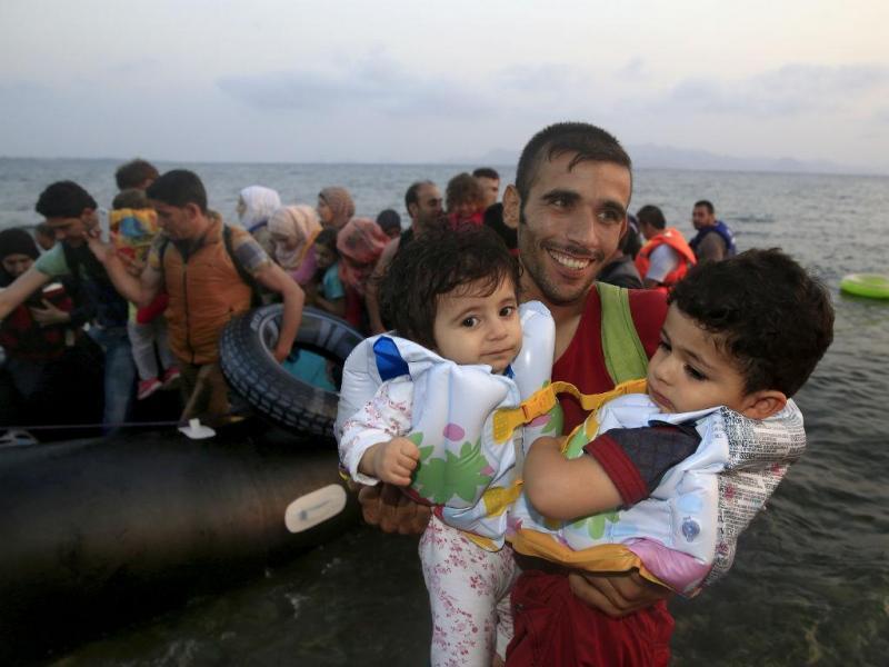 A alegria de chegar a terra. Refugiado sírio desembarca numa praia da Grécia com os filhos ao colo. Sobreviveram à travessia (REUTERS/Yannis Behrakis)