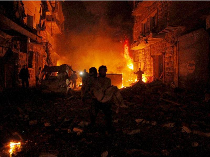 Homem transporta ferido enquanto grupos rivais batalham na Síria [Fonte: REUTERS/Sultan Kitaz]