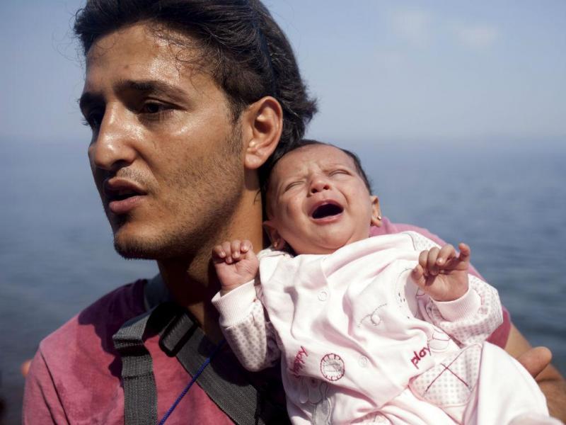 Refugiado sírio segura a filha de um mês, na chegada à ilha de Lesbos, na Grécia - Setembro de 2015 (REUTERS/Dimitris Michalakis)