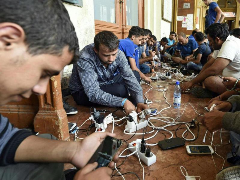 Migrantes e refugiados carregam os telemóveis na estação de Keleti (EPA)