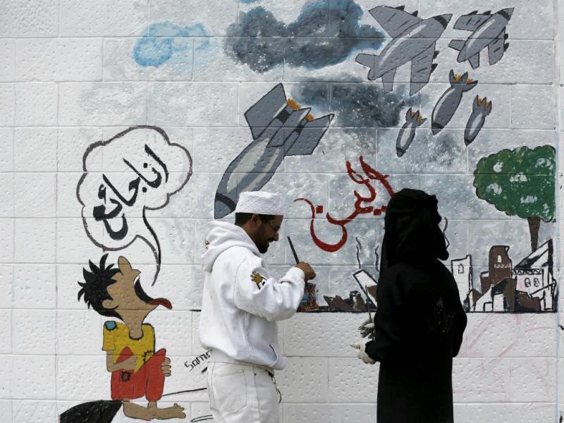 Ativistas pró-Houthis pintam um mural na embaixada da Arábia Saudita, em Sanaa, Iémen