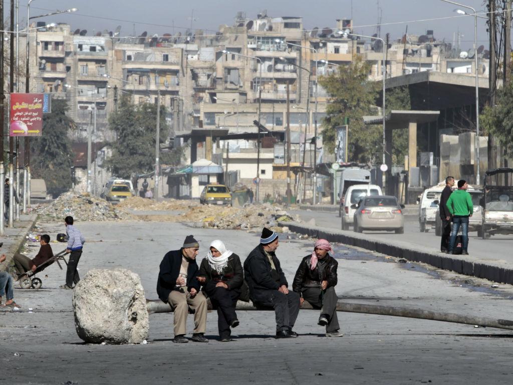 Homens sentados num destroço a guerra (REUTERS / Ahmed Jadallah)