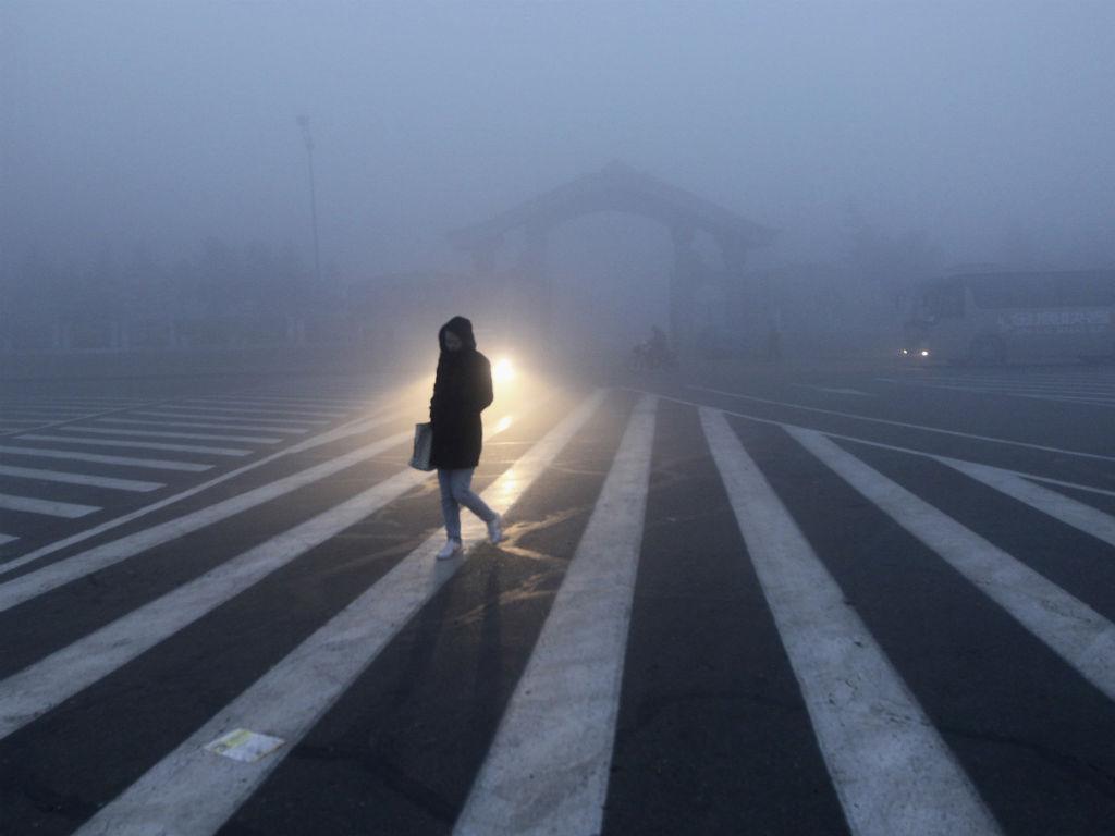 Uma mulher anda ao longo de uma rua durante um dia de poluição em Changchun, na província de Jilin (REUTERS / China Daily)