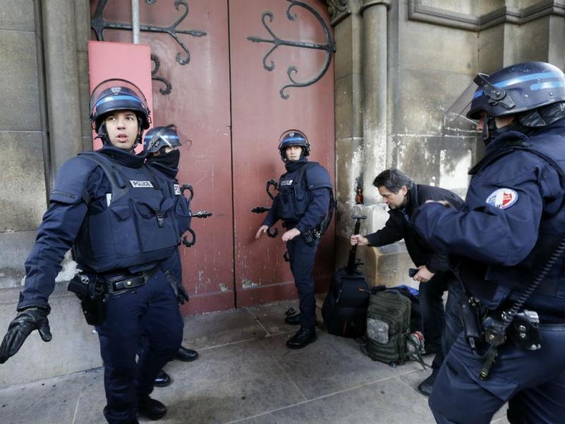 Polícia concentrada em frente à porta de uma igreja em Saint Denis, Paris, durante a caça aos jihadistas alegadamente responsáveis pelos atentados [Reuters]