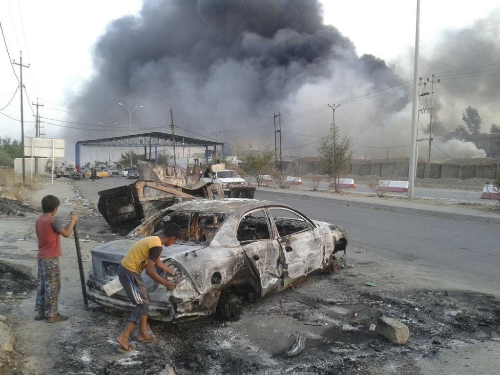 Crianças junto a um carro queimado, depois dos confrontos entre as forças iraquianas e o EI