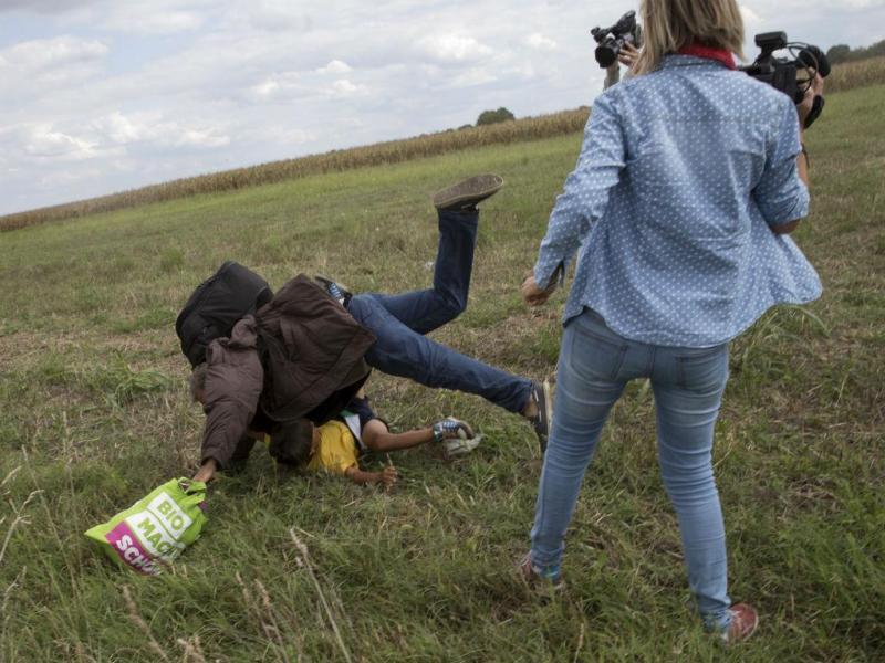 8 DE SETEMBRO: Jornalista húngara dá pontapés a refugiados que tentam entrar na Hungria. Petra Laszlo foi filmada a pregar uma rasteira a um homem que corria com um menino nos braços, em Röszke. A rasteira mudou a vida de Osama Abdul Mohsen. O sírio tombado com o filho de sete anos recebeu um convite de Espanha, para ali viver e ser treinador de futebol (REUTERS)