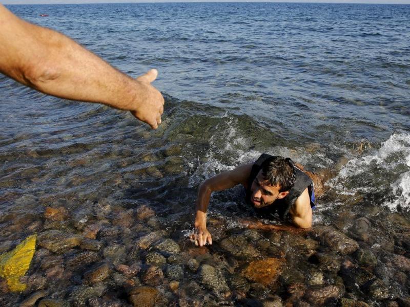 Homem ajuda refugiado sírio que nada exausto até praia na ilha grega de Lesbos, 17 setembro 2015