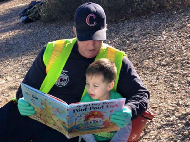 Bombeiro lê história a criança vítima de acidente (Reprodução Facebook)