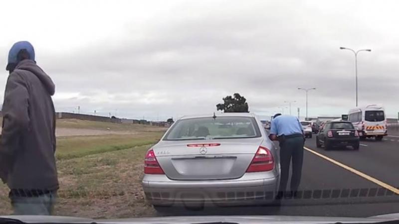 Atacante tenta desencravar a arma, enquanto o polícia, despercebido, passa a multa. (Reprodução Youtube)
