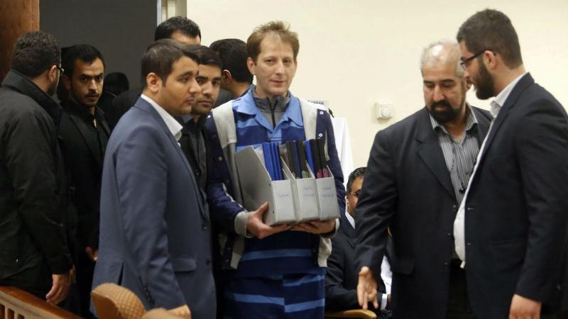Babak Zanjani, ao centro na imagem, usando o uniforme prisional, durante o julgamento